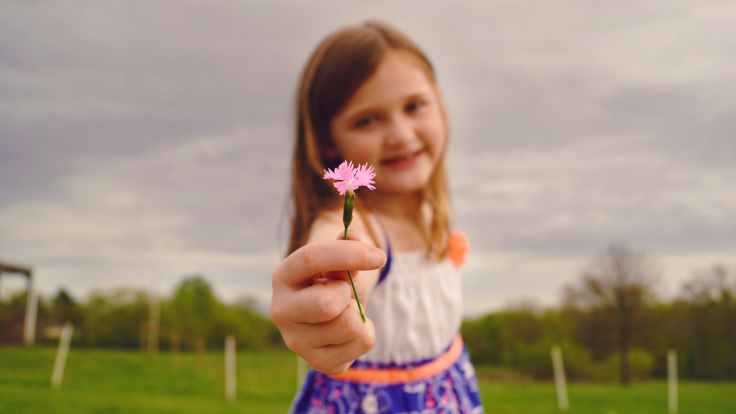 selective focus photography of girl holding pink flower