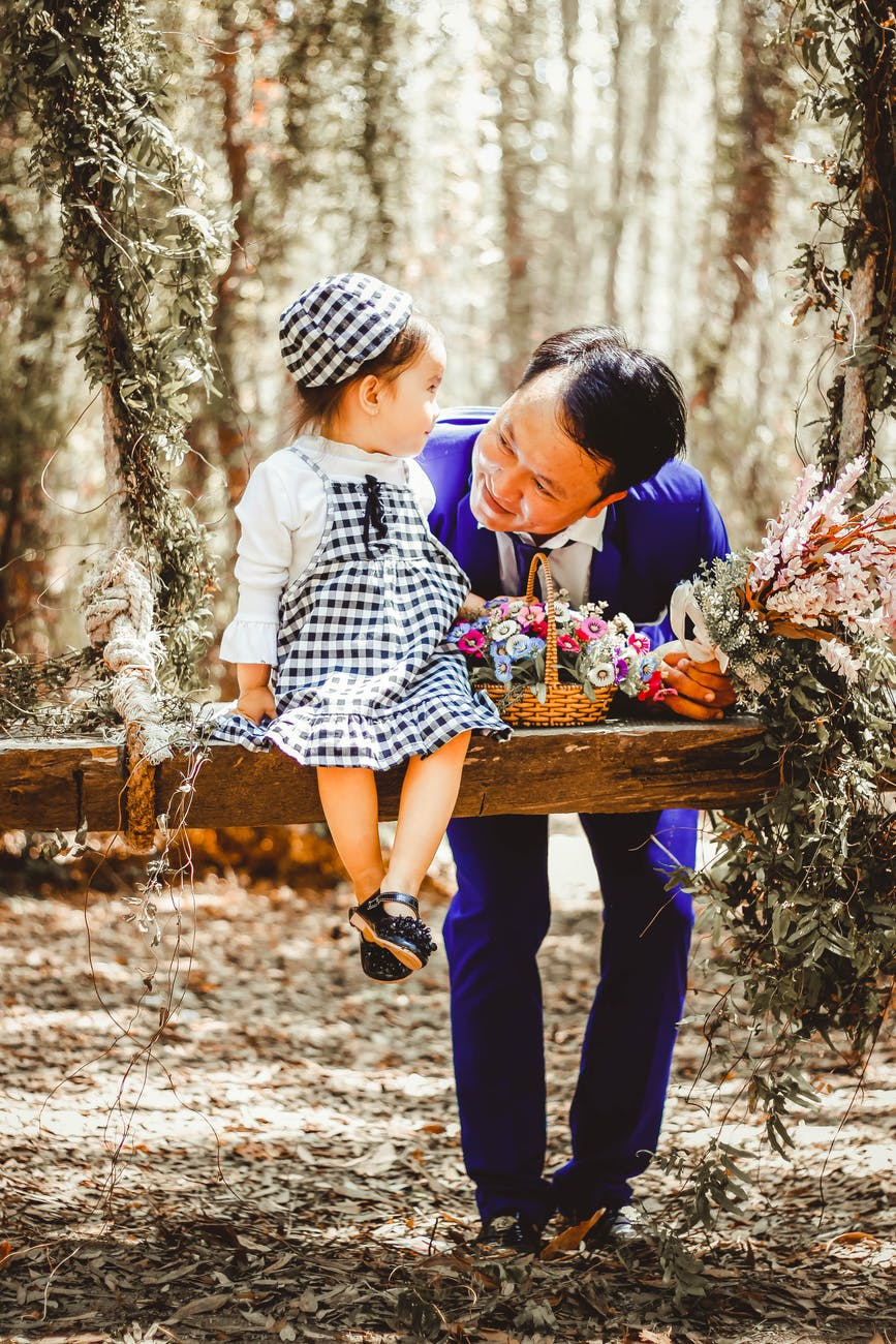 selective focus and color photography of man looking at her girl sitting on garden swing white holding bouquet of flower in brown wicker basket