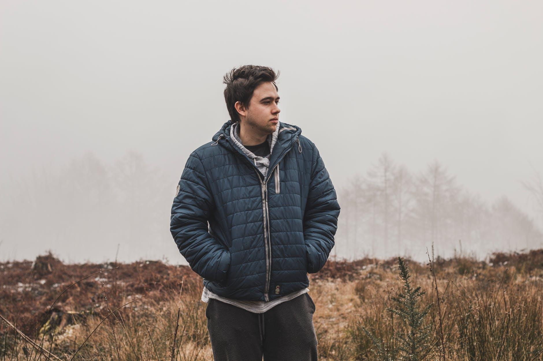 man wearing black zip up hooded jacket standing