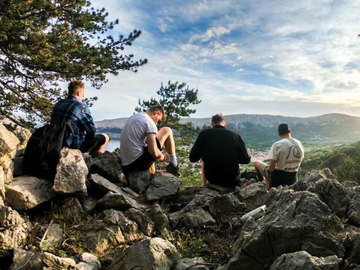 four men seated on rocks facing mountain