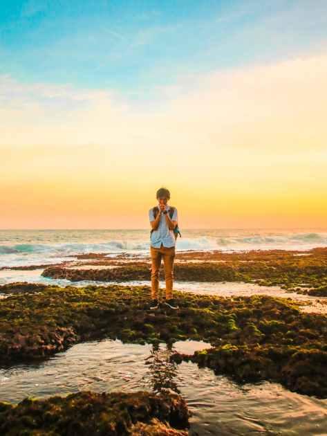 man standing on rocks near beach during golden hour