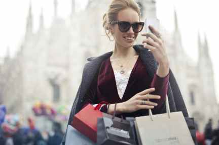 woman in maroon long sleeved top holding smartphone with shopping bags at daytime