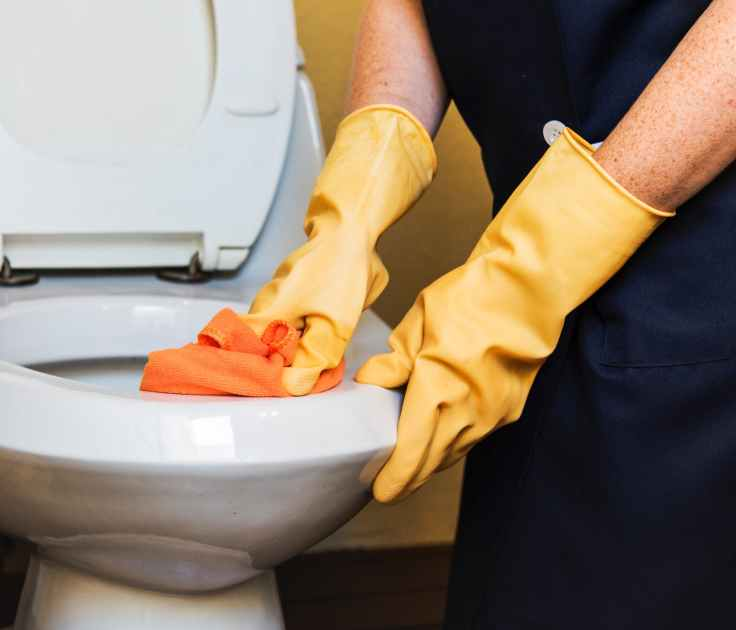 person wearing pair of yellow rubber gloves