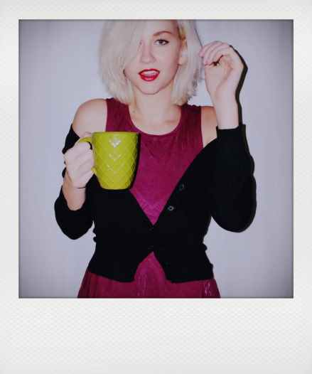 woman holding ceramic mug while smiling photo