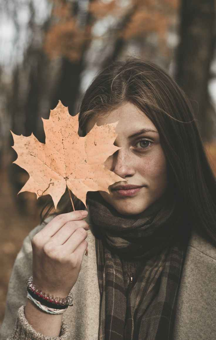 woman holding orange maple leaf