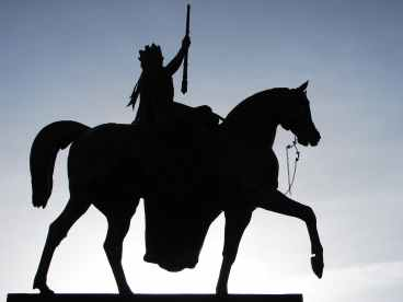 silhouette of man holding rifle riding on horse